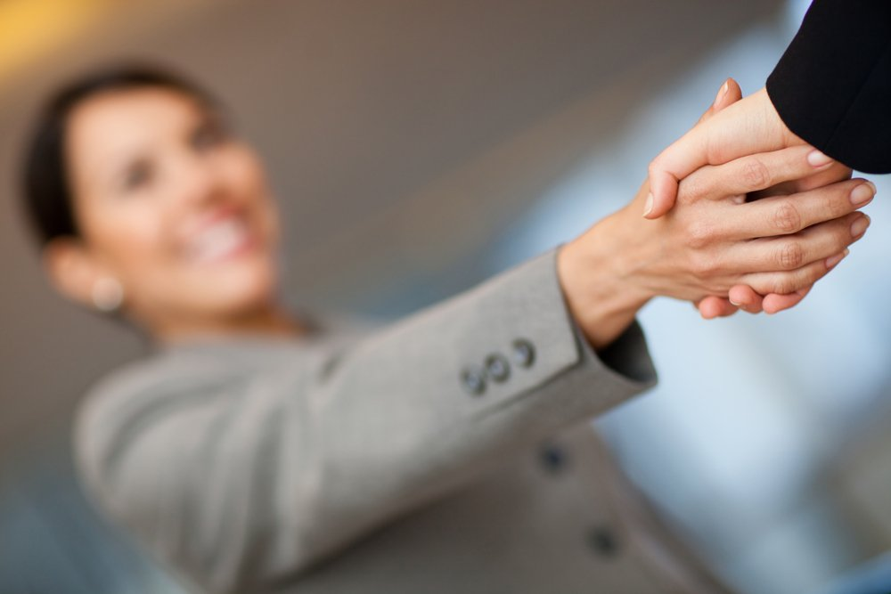Welcoming business woman giving a handshake and smiling